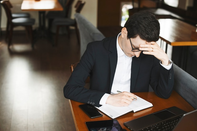 커피 숍에 앉아 노트북에 쓰는 동안 생각하고 자신감 사업가의 측면보기 초상화.