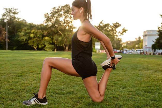 Портрет женщины фитнеса в наушниках взгляда со стороны