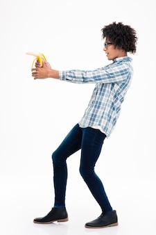 흰 벽에 고립 된 바나나에서 목표로 재미있는 아프리카 계 미국인 남자의 측면보기 초상화