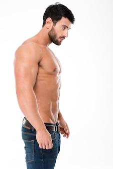 Вид сбоку портрет красивого мужчины с мускулистым телом, стоящим изолированным на белой стене