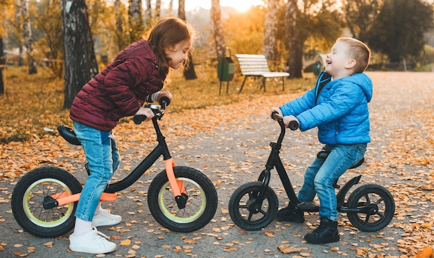 Портрет вид сбоку прекрасного брата и сестры, сидящих лицом к лицу на велосипедах, смеясь над закатом.