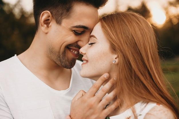 그의 친구의 얼굴을 만지고있는 동안 키스하기 전에 웃는 닫힌 눈으로 얼굴을 맞대고 데이트하는 사랑스러운 부부의 측면보기 초상화.