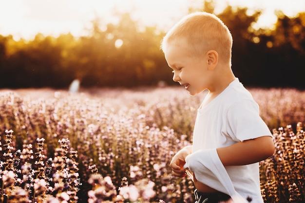 Портрет вид сбоку милого маленького ребенка, играющего в био-поле цветов, улыбаясь против заката.