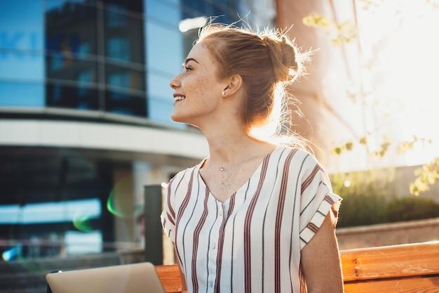 일몰에 건물에 대 한 그녀의 노트북에서 일하는 벤치에 앉아있는 동안 웃 고 사랑스러운 젊은 여성 프리랜서의 측면보기 초상화.