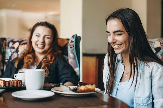 커피 숍에서 그녀의 친구와 함께 앉아있는 동안 눈으로 웃고 검은 긴 머리를 가진 사랑스러운 젊은 여성의 측면보기 초상화.