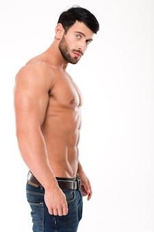 Портрет вид сбоку мускулистого мужчины, смотрящего на фронт, изолированного на белой стене