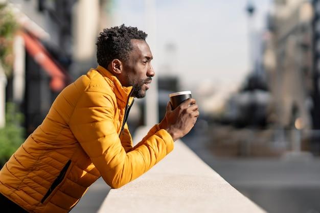 街の景色を考えているコーヒーのカップを保持しているバルコニーに寄りかかっている深刻なアフリカ人の側面図の肖像画