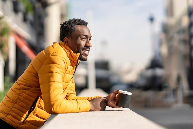 街の景色を考えているコーヒーのカップを保持しているバルコニーに寄りかかって笑顔のアフリカ人の側面図の肖像画