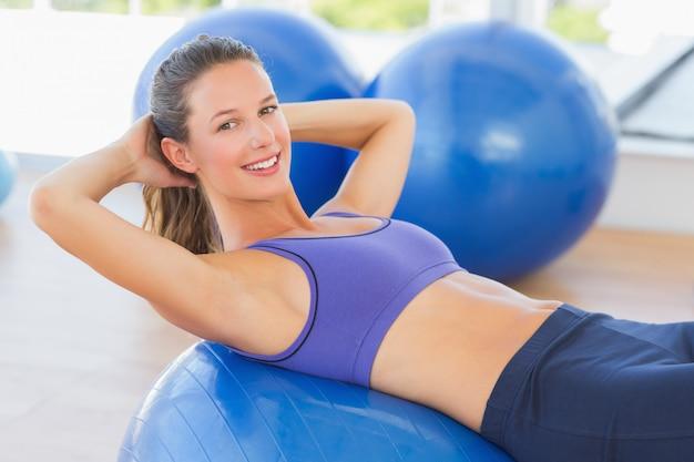 運動のボールに横たわっている笑顔の女性の側面の肖像画