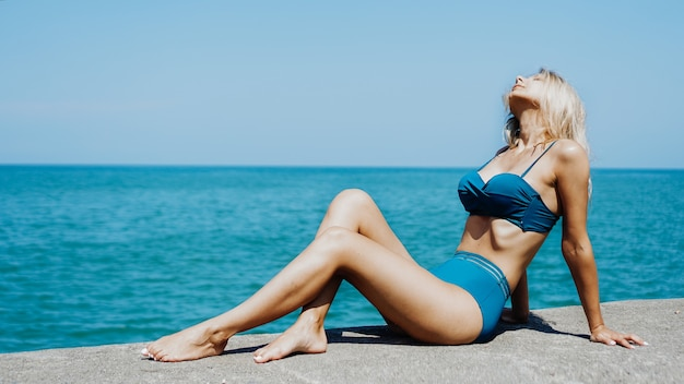 해변에서 신선한 공기를 마시며 휴식을 취하는 여성의 옆모습 초상화