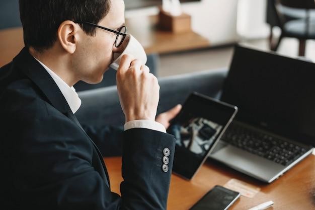 안경을 쓰고 커피를 마시고 커피 숍에서 태블릿에서 작동하는 양복을 입은 젊은 백인 프리랜서의 측면보기 초상화.