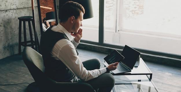 Портрет вид сбоку молодой, одетой в костюм владельца, сидящего в своем офисе, работая во время разговора на смартфоне и глядя на экран планшета.