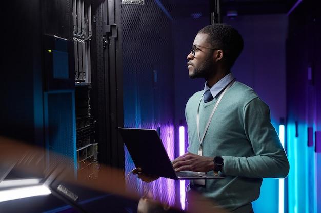 Портрет вид сбоку афро-американского инженера данных, держащего ноутбук во время работы с суперкомпьютером в серверной комнате, освещенной синим светом, копией пространства