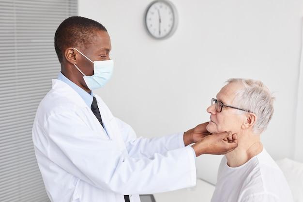 Вид сбоку портрет афро-американского врача, осматривающего старшего мужчину в белой больничной палате, копией пространства
