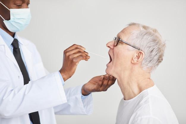 백인에 대해 병원에 있는 노인의 covid 검사를 받는 아프리카계 미국인 의사의 측면 초상화