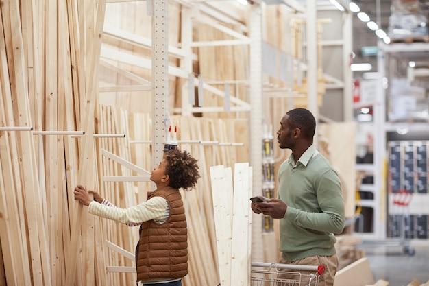 Портрет вид сбоку афро-американских отца и сына, делающих покупки вместе в строительном магазине, фокус на мальчике, выбирающем деревянные доски для строительства, копировальное пространство