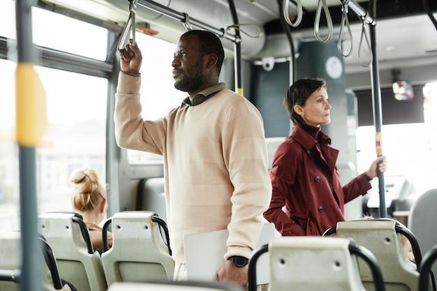 Портрет вид сбоку афроамериканца, держась за перила в автобусе во время поездки на общественном транспорте по городу, копия пространства
