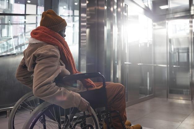 Портрет вид сбоку афроамериканца в инвалидной коляске, входящего в доступный торговый центр или станцию метро в городских условиях города, копия пространства