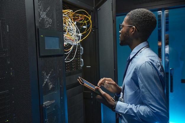 Портрет вид сбоку афроамериканца, стоящего у серверного шкафа во время работы с суперкомпьютером в центре обработки данных и держащего планшет, копировальное пространство