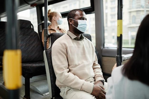Портрет вид сбоку афро-американского мужчины в маске в автобусе во время поездки на общественном транспорте по городу, копией пространства