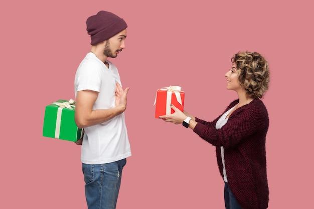 캐주얼한 스타일로 서 있는 놀라운 친구 커플의 측면 초상화, 선물 상자를 주는 소녀, 선물 뒤에 숨어 있는 소년, 기념일을 축하합니다. 절연, 실내, 스튜디오 촬영, 분홍색 배경