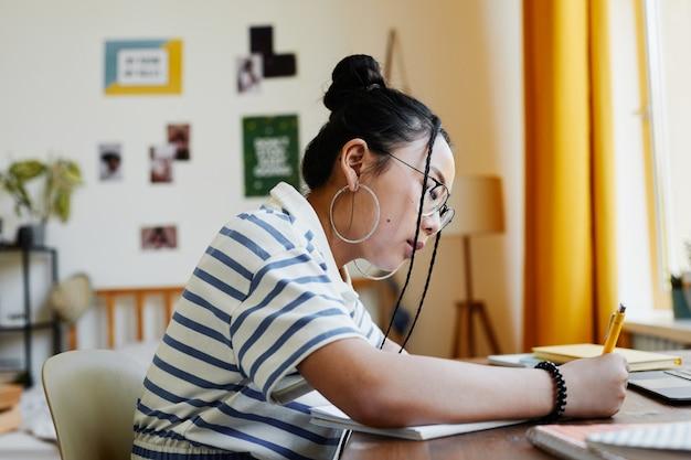Вид сбоку портрет азиатской девочки-подростка, которая учится за столом у себя дома и пишет в записной книжке, копией пространства