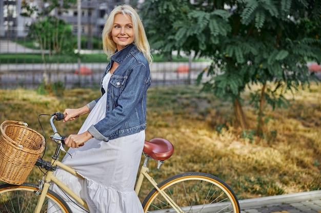 세련된 흰색 긴 드레스를 입은 매력적인 금발 백인 여성의 측면 보기 초상화는 바구니가 달린 도시 자전거 핸들에 손을 잡고 있습니다.