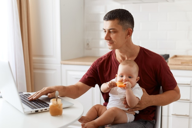カジュアルなスタイルの栗色のtシャツを着て、仕事と彼の小さな赤ん坊の娘の世話をし、ポータブルコンピューターで入力して、魅力的なブルネットの男性フリーランサーの側面図の肖像画。
