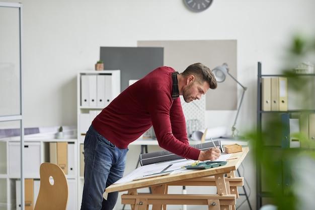 직장에서 책상에 기대어 청사진을 그리는 수염 된 건축가의 측면보기 초상화,