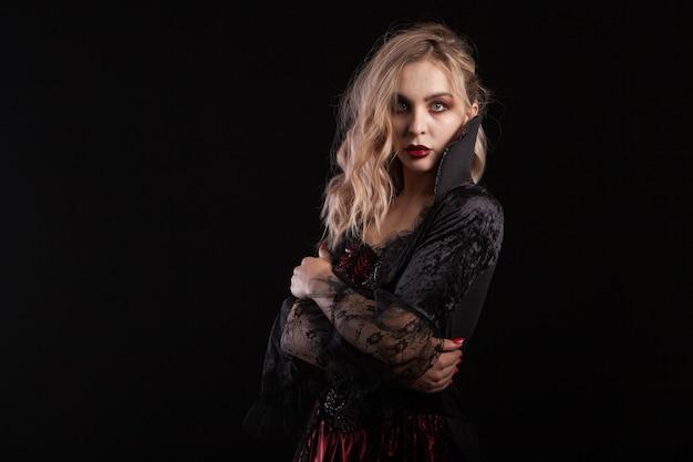 ハロウィーンのカーニバルの吸血鬼のようにドレスアップした美しい金髪の女性の側面図の肖像画。スタイリッシュな吸血鬼の女性。