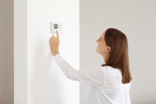 흰색 캐주얼 스타일의 셔츠를 입은 검은 머리를 한 아름다운 여성의 측면 초상화, 밝은 방에 실내에 서서 온도 조절 장치로 집의 중앙 난방 온도를 조정합니다.