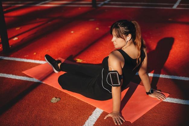 스포츠 공원에서 야외 체중 감량 운동을 한 후 멀리 restring 찾고 아름다운 젊은 몸 긍정적 인 여자의 측면보기 초상화.