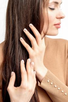 Вид сбоку портрет красивой молодой кавказской брюнетки с закрытыми глазами, касающейся ее волос ухоженными пальцами на белой стене