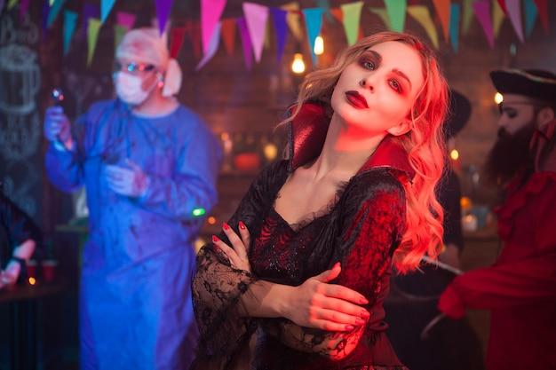 ハロウィーンの集まりで真面目な顔をした魔女のような格好をした美しい若い女性の側面図の肖像画。男はハロウィーンのお祝いでバックグラウンドで医者のようにドレスアップしました。