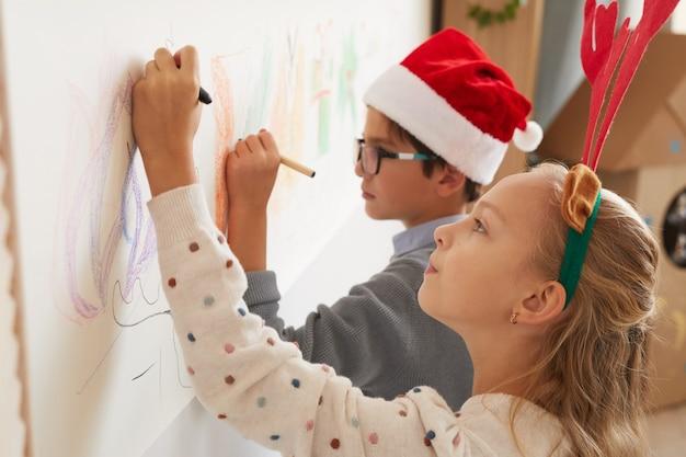 Портрет мальчика и девочки, рисующие на стенах в шляпах и рогах санта-клауса на рождество, вид сбоку, копия пространства