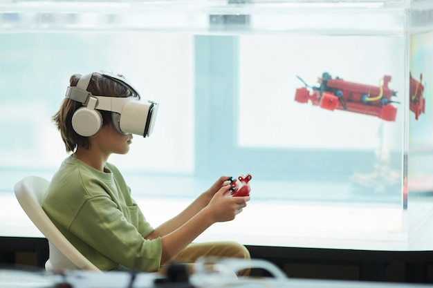 학교 실험실에서 로봇 보트를 작동하는 동안 vr 헤드셋을 착용한 소년의 측면 보기 초상화, 복사 공간