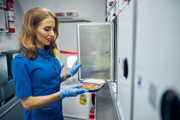 손에 음식을 들고 공기 부엌에 서있는 매력적인 승무원의 측면보기 초상화