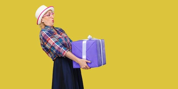 흰 모자와 체크무늬 셔츠를 입은 경쾌한 현대 할머니의 옆모습 초상화가 서 있고 크고 무거운 선물 상자를 들고 인사를 하려고 합니다. 스튜디오 촬영, 노란색 배경, 절연