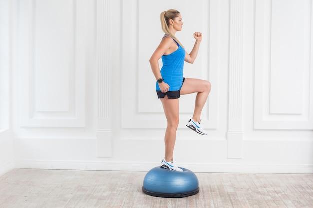 검은 반바지를 입고 체육관에서 일하는 파란색 탑을 입은 스포티하고 아름다운 젊은 운동 금발 여성의 측면 초상화는 피트니스 공에서 한쪽 무릎을 들어올렸습니다.