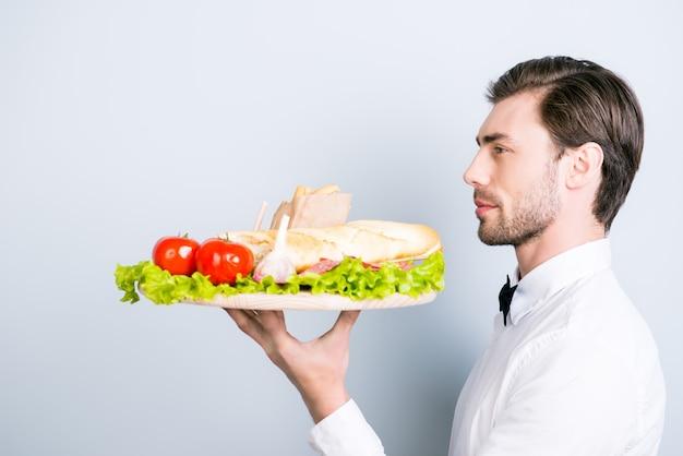 Вид сбоку портрет уверенного молодого официанта, несущего заказ
