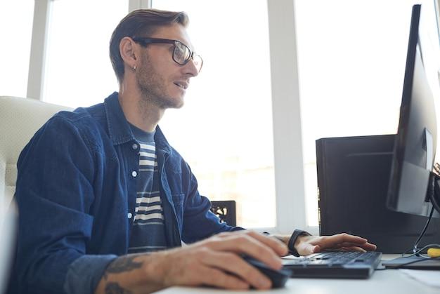 Вид сбоку портрет современного татуированного человека, использующего компьютер во время работы за столом дома или в офисе против окна