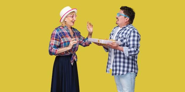 행복한 친구 커플, 캐주얼한 체크무늬 셔츠를 입은 남녀, 흥분한 여성에게 현재 선물 상자를 주는 남편의 측면 초상화. 실내, 절연, 스튜디오 촬영, 노란색 배경