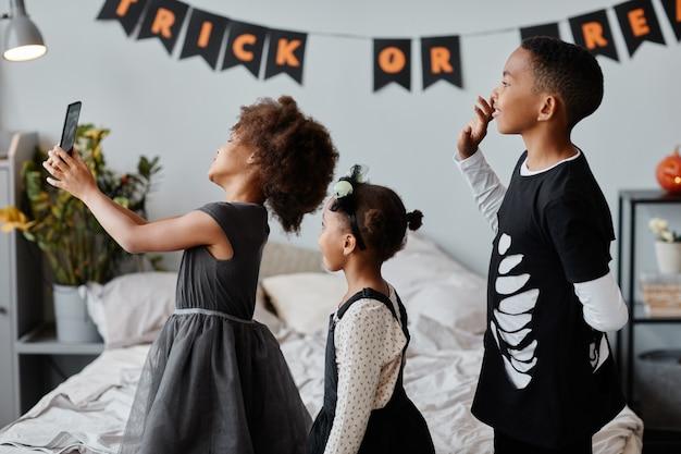집에서 할로윈 의상을 입고 손을 흔드는 귀여운 아프리카계 미국인 아이들의 측면 초상화