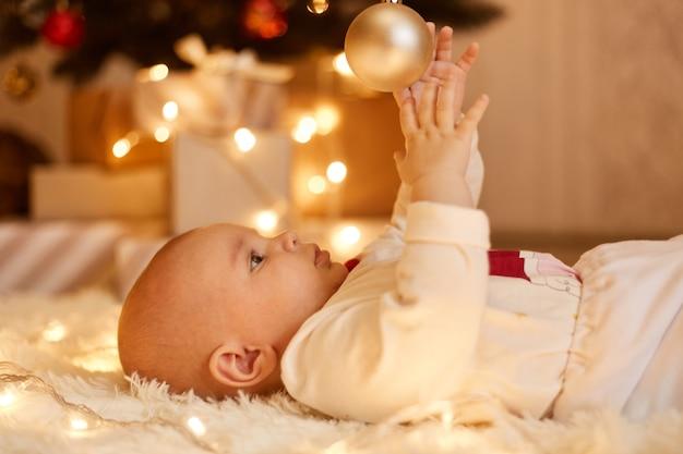 クリスマスツリー、大晦日のお祝い、屋内ショットからボールで遊んで柔らかいカーペットの上に床に横たわっているかわいい魅力的な幼児の女の子の側面図の肖像画。