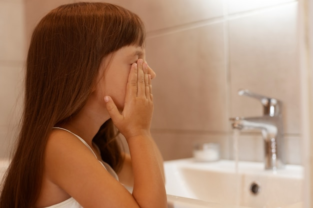 Портрет вид сбоку темноволосой девочки, умывающей лицо в ванной после пробуждения утром, стоя в ванной возле крана и раковины.