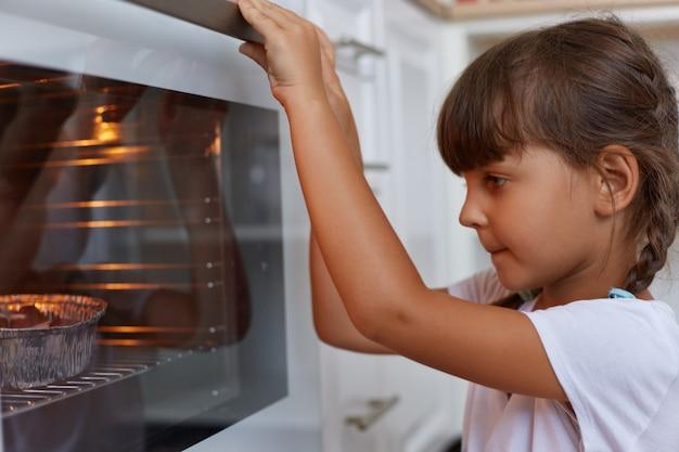 Портрет темноволосой девочки с косичками в белой футболке, вид сбоку, сидящей возле газовой плиты и смотрящей внутрь духовки, ожидающей готовности выпечки,