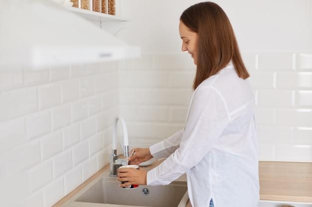Портрет вид сбоку темноволосой женщины в белой рубашке, стоящей возле кухонного гарнитура, наливая воду из крана на кухне, мыть кружку, позирует в светлой комнате.