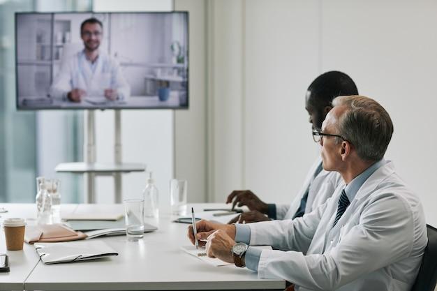 会議室の会議テーブルに座って、オンラインプレゼンテーション、コピースペースを聞いている医師の側面図の肖像画