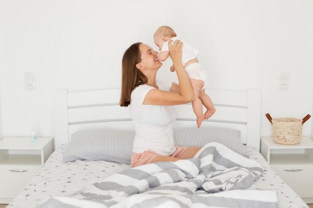 흰색 캐주얼 스타일의 티셔츠를 입고 검은 머리를 하고 손을 들고 침대에 앉아 있는 동안 집에서 유아와 노는 아기 딸을 안고 있는 매우 행복한 어머니의 측면 초상화.