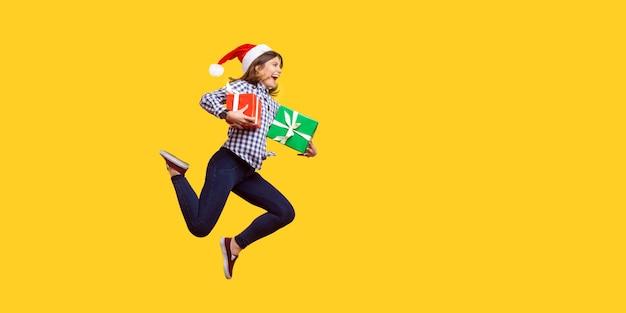 산타 모자를 쓰고 점프하거나 포장된 크리스마스 선물 상자를 들고 공중에서 뛰어다니는 매우 즐거운 브루네트 여성의 측면 초상화는 할인을 축하합니다. 노란색 배경에 고립 된 실내 스튜디오 촬영